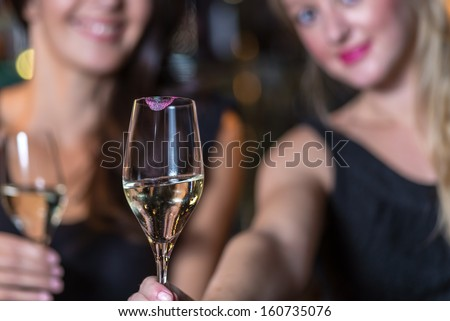 Happy smiling women celebrating with champagne in a restaurant or nightclub while out partying with focus to the elegant glass of champagne in the foreground - stock photo