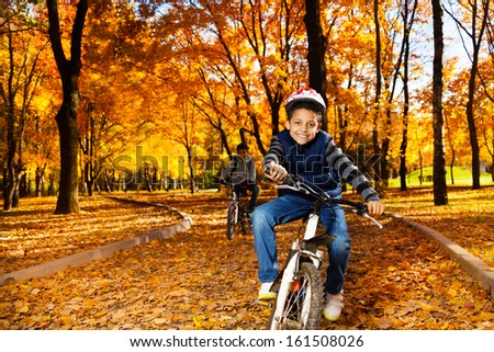 Happy smiling 8 years old black boy riding a bike in the autumn park with his brother