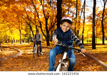 Happy smiling 8 years old black boy riding a bike in the autumn park with his older brother