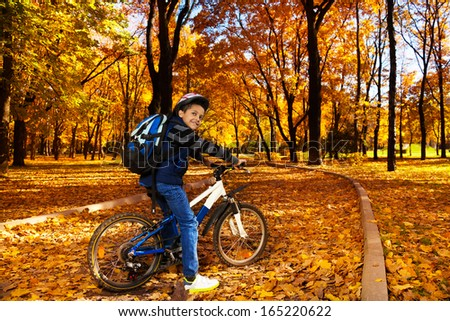 Happy smiling 8 years old black boy with backpack riding a bike in the autumn park leaning on bicycle stern turning back