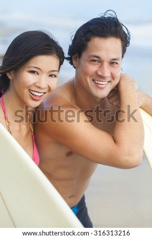 Happy smiling young Asian man & woman, boy & girl, couple on a beach surfing with surfboards - stock photo
