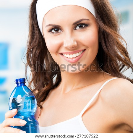 Happy smiling young attractive woman with bottle of water, at fitness club or gym - stock photo