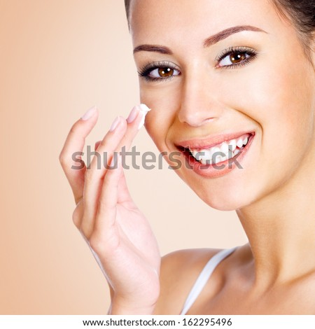 Happy smiling young beauitful woman applying cream on the face