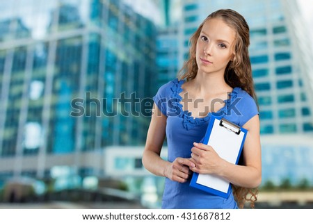 Happy smiling young beautiful business woman with clipboard