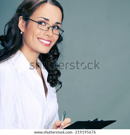 Happy smiling young beautiful business woman with clipboard writing, over gray background - stock photo