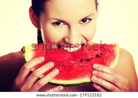 Happy, smiling young beautiful woman is eating watermelon.