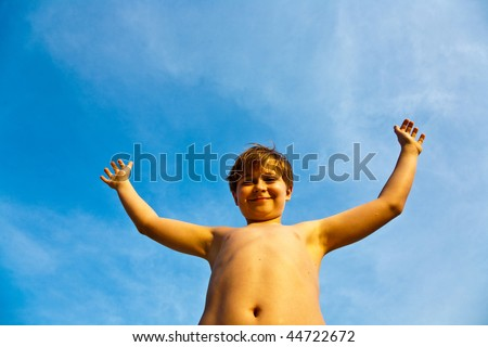 happy smiling young boy with background blue sky rises up his arms