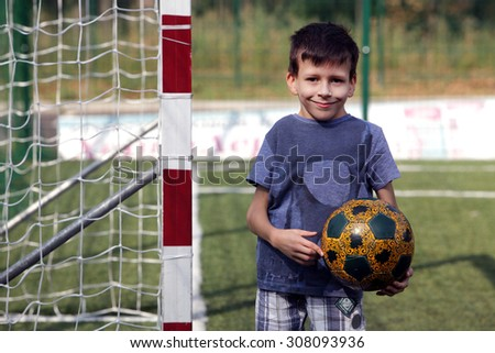 Happy smiling young boy with football ball standing near gates - stock photo
