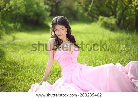 Happy smiling young bride girl dreaming and resting on green grass at spring park. Attractive brunette model wearing in pink wedding dress. - stock photo