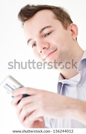 Happy smiling young brown-haired businessman writing sms text message on the mobile phone and enjoy the success on isolated white background