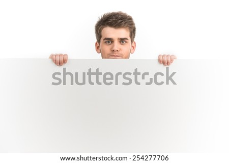 Happy smiling young business man showing blank signboard. Portrait Of Young Man Holding Placard Isolated On White Background  - stock photo