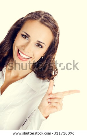 Happy smiling young business woman showing blank area for sign or copyspase