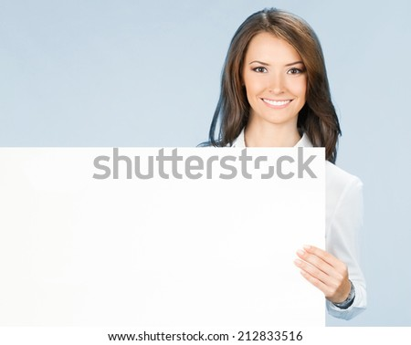 Happy smiling young business woman showing blank signboard, over blue background - stock photo