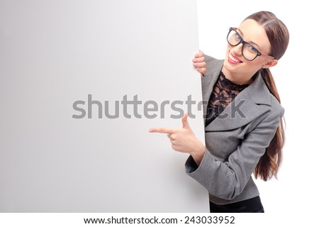 Happy smiling young business woman wearing glasses showing blank signboard pointing with her finger, isolated on white background - stock photo