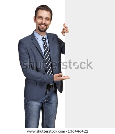 Happy smiling young businessman showing large blank grey signboard isolated on white background - stock photo