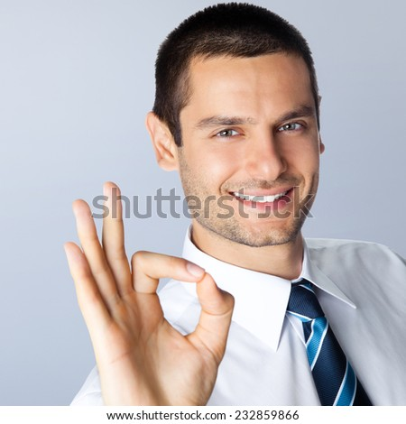 Happy smiling young businessman with okay gesture, against grey background - stock photo
