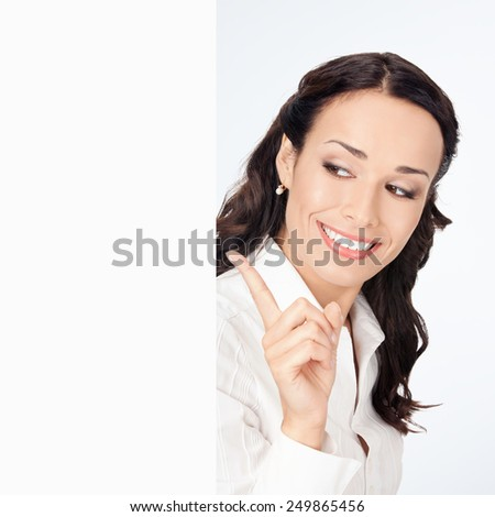 Happy smiling young businesswoman showing blank signboard, against grey background, with copyspace