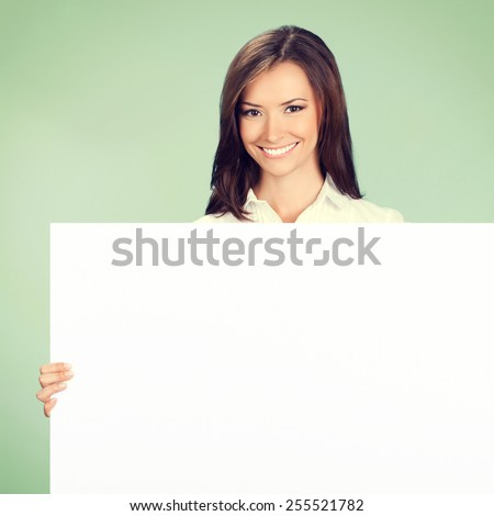 Happy smiling young businesswoman showing blank signboard with copyspace area for text or slogan, on green background