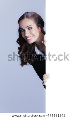 Happy smiling young businesswoman showing blank signboard, with empty copyspace area for slogan or advertising text message. Brunette woman in business concept studio shoot.