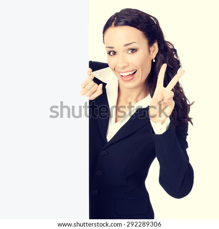 Happy smiling young businesswoman with blank signboard, showing two fingers - stock photo