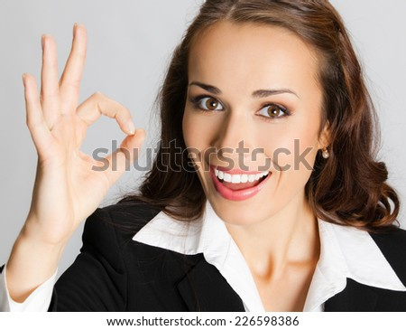 Happy smiling young businesswoman with okay gesture, against grey background - stock photo