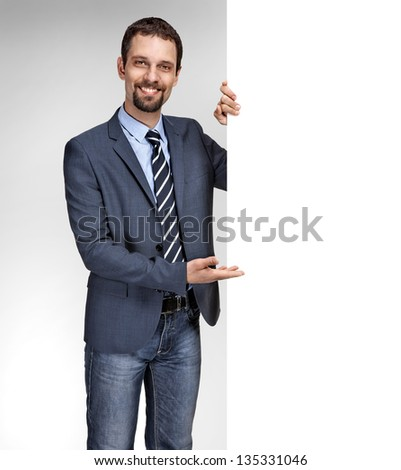 Happy smiling young caucasian businessman showing large blank signboard isolated on grey background - stock photo