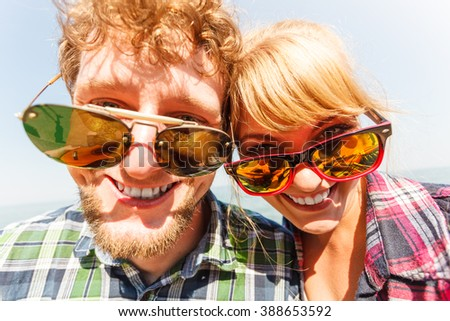 Happy smiling young couple outdoor. Pretty attractive woman and handsome man in sunglasses. - stock photo
