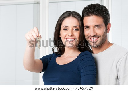 Happy smiling young couple showing a pair of keys of their new house - stock photo