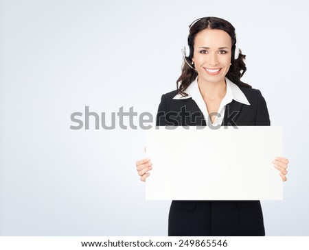 Happy smiling young customer support phone operator in headset showing blank signboard, against grey background, with copyspace - stock photo