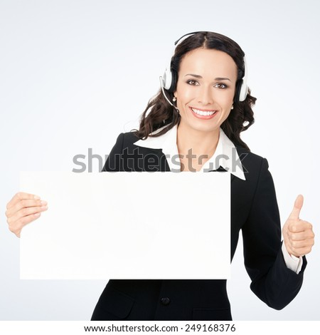 Happy smiling young customer support phone operator in headset showing blank signboard with thumbs up, against grey background, with copyspace