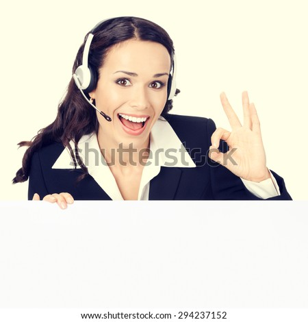 Happy smiling young customer support phone operator or businesswomen in headset showing blank signboard with okay hand sign gesture - stock photo