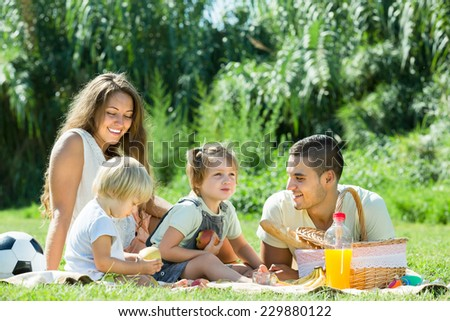 Happy smiling young family of four having picnic at meadow in park  - stock photo