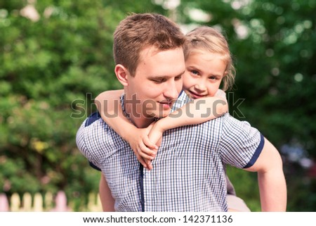 Happy smiling young father and daughter playing in the park - stock photo