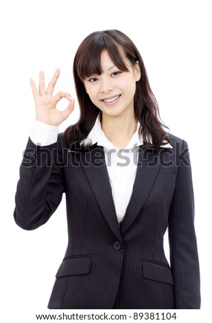 Happy smiling young japanese business woman with okay gesture - stock photo