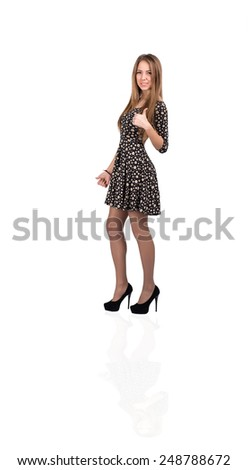 Happy smiling young lady with OK hand sign. Full body portrait of young Caucasian lady makes OK hand sign. Bright casual dress and white background, with light reflection on the floor - stock photo