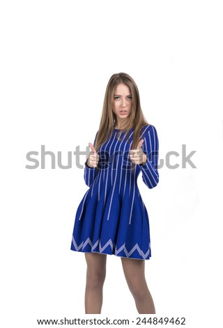 Happy smiling young lady with OK hand sign. Young Caucasian lady makes OK hand sign. Bright blue dress and white background. - stock photo