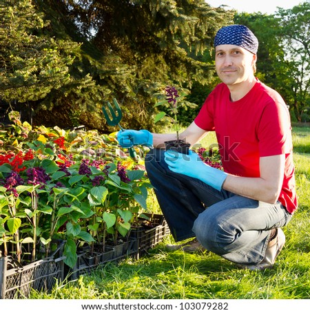 Happy smiling young man gardening - planting flowers - stock photo