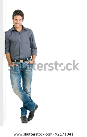 Happy smiling young man leaning against white wall with copy space an the right