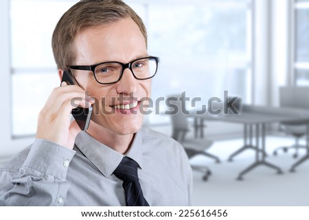 Happy smiling young man talking on mobile in the office - stock photo
