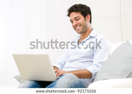 Happy smiling young man watching and working on computer laptop at home