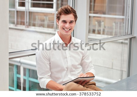 Happy smiling young man with tablet indoor