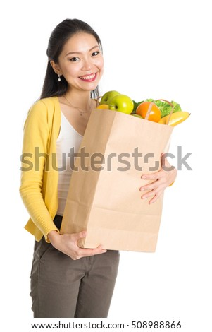 Happy smiling young pan Asian woman holding paper shopping bag full of groceries isolated on white background.
