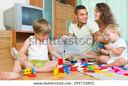 Happy smiling young parents and two daughters relaxing with toys in home