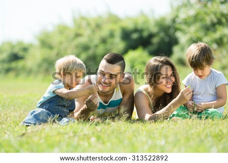 Happy smiling young parents with two kids lying on grass in sunny summer park