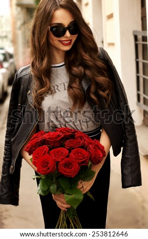 Happy smiling young pretty beautiful woman wearing stylish skirt, t-shirt, leather jacket and sunglasses and holding red roses bouquet - stock photo