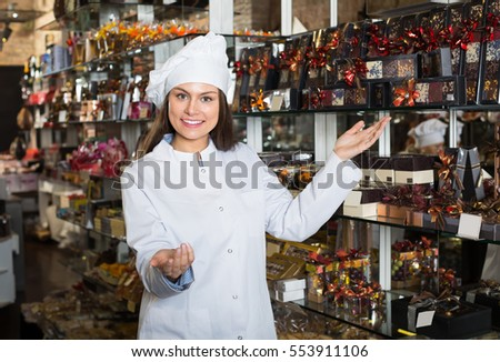 Happy smiling young shopgirl posing with different delicious chocolate and confectionery at display