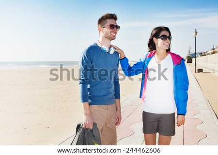 Happy smiling young tourist couple on their summer vacation standing on a beach boardwalk holding a backpack or bag on a hot summer day smiling as they look off to the right of the frame - stock photo