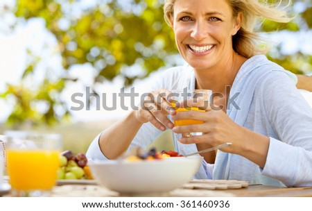 Happy Smiling Young Woman Eating Fruits - stock photo