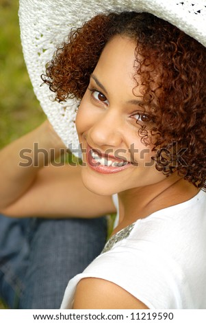 Happy, smiling young woman hanging out in the backyard in a big summer hat - stock photo