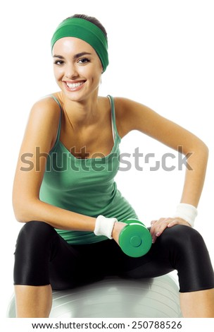 Happy smiling young woman in green fitness wear exercising with dumbbell and fitball, isolated against white background - stock photo